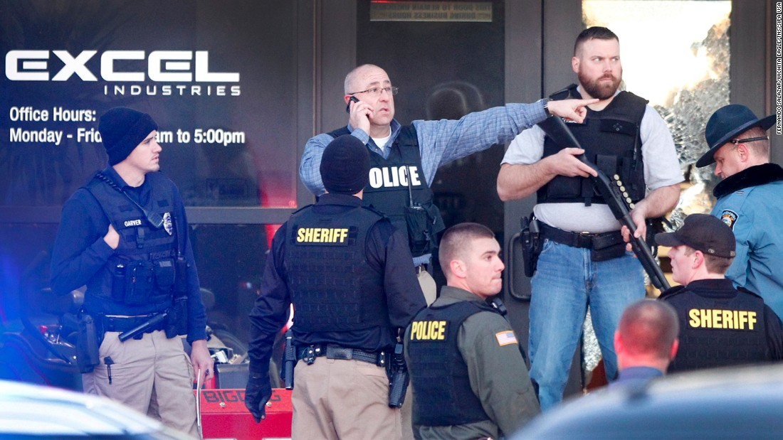 Several officers stand at the front door of Excel Industries in Hesston, Kansas, where a series of shootings that left multiple dead ended on Thursday, February 25. The suspected shooter, an employee at Excel, was killed by authorities.