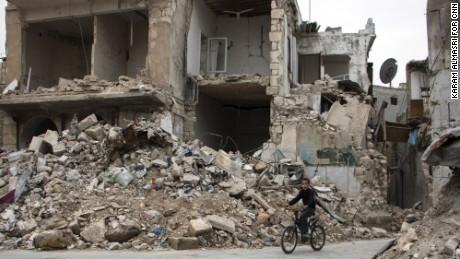 A boy cycles through Aleppo.