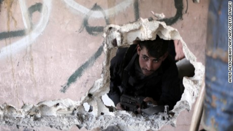 A Syrian rebel fighter from the Failaq al-Rahman brigade mans a position on the frontline against regime forces in the town of Arbin in the eastern Ghouta region on the outskirts of the capital Damascus on February 26, 2016.  A partial ceasefire between Syria's regime forces and non-jihadist rebel fighters is due to take effect at midnight (2200 GMT) local time.  / AFP / AMER ALMOHIBANY        (Photo credit should read AMER ALMOHIBANY/AFP/Getty Images)