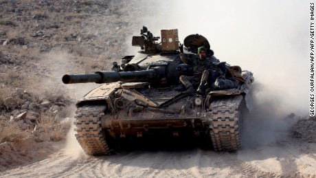 """Syrian government forces drive a tank on a road during a military operation against the Islamic State (IS) group in the villages of Zarour and Khanaser, in the Aleppo governorate, on February 26, 2016.  With the ceasefire due to take effect at 2200 GMT, US President Barack Obama has warned Damascus and key ally Moscow that the """"world will be watching"""". Both President Bashar al-Assad's regime and the main opposition body have agreed to the deal -- which allows fighting to continue against the Islamic State group and other jihadists.  / AFP / GEORGES OURFALIAN        (Photo credit should read GEORGES OURFALIAN/AFP/Getty Images)"""