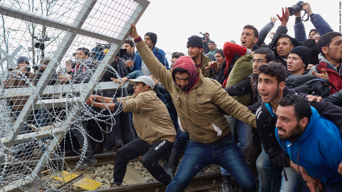 Refugees break through a barbed-wire fence on the Greece-Macedonia border on Monday, February 29, as tensions boil over regarding new travel restrictions into Europe.