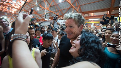 SINGAPORE - JULY 05:  British chef Gordon Ramsay poses with a fan as he visits the Tian Tian chicken rice stall at the Maxwell Food Centre to learn about the dish on July 5, 2013 in Singapore. Celebrity chef Ramsay is in Singapore to accept a challenge from a group of food-loving Singaporean bloggers for a culinary contest. Ang Kiam Meng from Jumbo Seafood, Foo Kui Lian from Tian Tian Chicken Rice and Ryan Koh from 328 Katong Laksa will go up against Ramsay  (Photo by Nicky Loh/Getty Images)