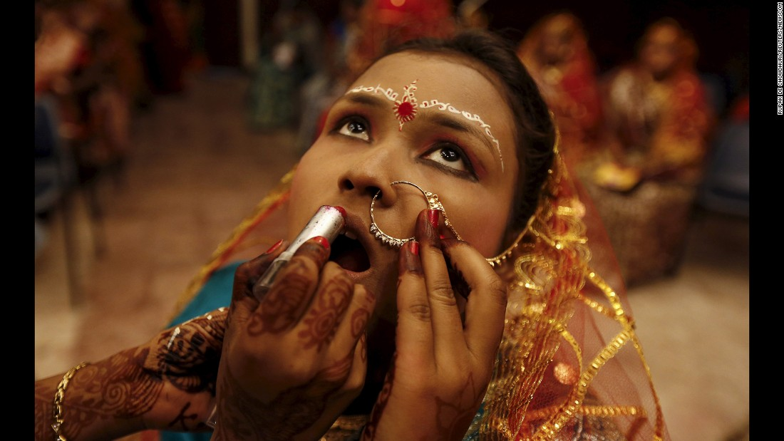 A bride has makeup applied before the start of a daylong mass marriage ceremony featuring 150 Hindu, Muslim and Christian couples from villages across the state.