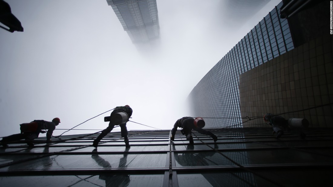 Workers clean the Shanghai World Financial Center in the financial district of Pudong. Shanghai Tower is seen at the top of the picture, and Jin Mao Tower is to the left.