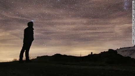 A photographer looks at the sky at night to see the annual Geminid meteor shower on the Elva Hill, in Maira Valley, near Cuneo, northern Italy on December 12, 2015.  AFP PHOTO / MARCO BERTORELLOMARCO BERTORELLO/AFP/Getty Images