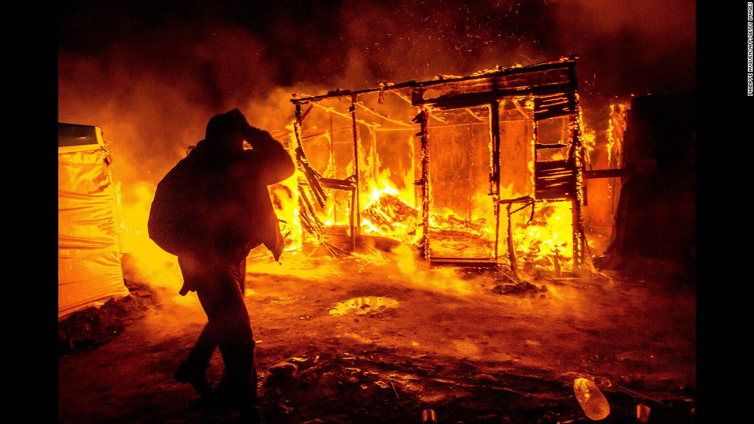 """A migrant walks past a burning shack in the southern part of the """"Jungle"""" migrant camp in Calais, France, on Tuesday, March 1. Part of the camp is being demolished and the inhabitants relocated in response to unsanitary conditions at the site."""