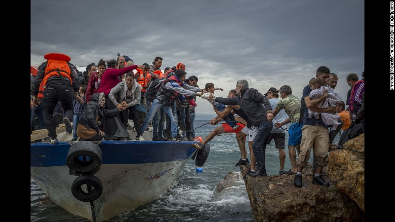 Refugees and migrants get off a fishing boat at the Greek island of Lesbos after crossing the Aegean Sea from Turkey in October 2015. More than 1 million refugees and migrants escaped to Europe in 2015, the UN refugee agency said.