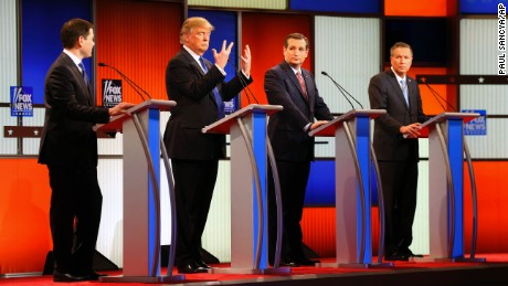 Republican presidential candidate, businessman Donald Trump, second from left, gestures as Sen. Marco Rubio, R-Fla., Sen. Ted Cruz, R-Texas, and Ohio Gov. John Kasich watch him a Republican presidential primary debate at Fox Theatre, Thursday, March 3, 2016, in Detroit