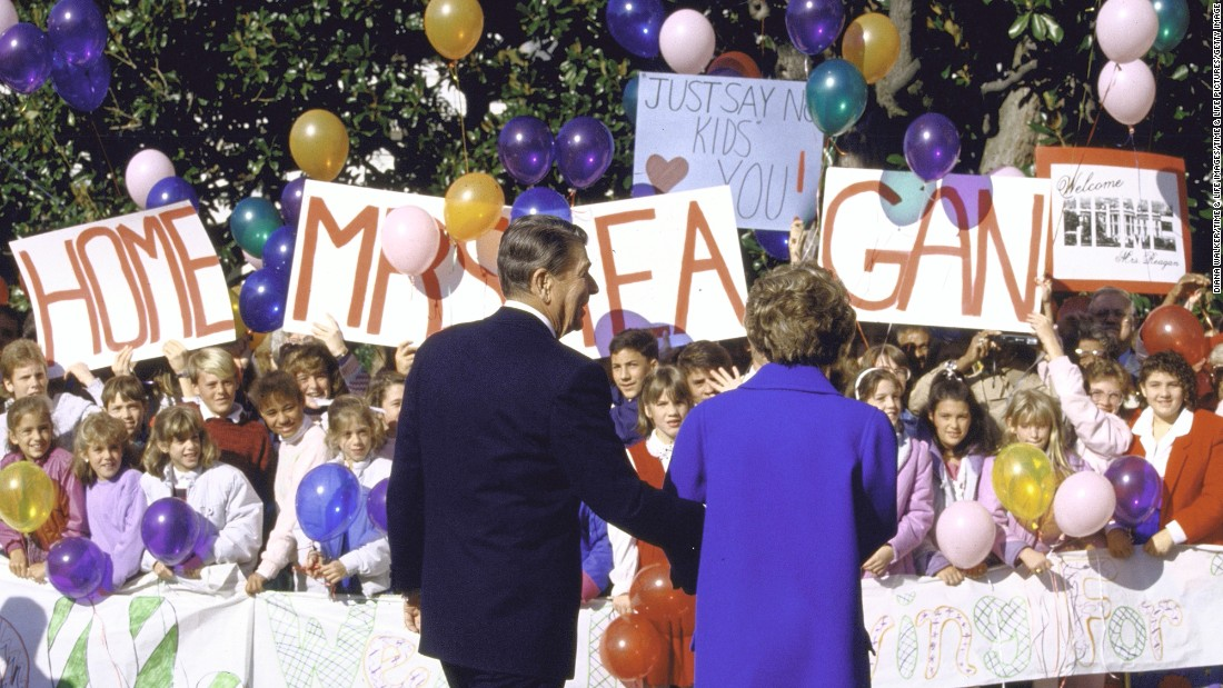 The Reagans are welcomed by youngsters with signs and balloons as Nancy returns to the White House after undergoing a mastectomy in October 1987.