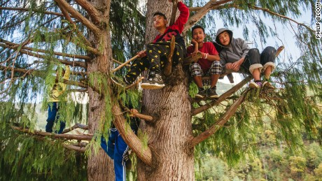 A group of children huddle together on a tree for a better vantage point of a music festival outside the capital city of Thimphu. Recent advances in technology have introduced Bhutanese artists to more modern forms of music, including rappers inspired by Eminem.