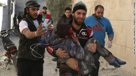 Men treat a child after an airstrike on a residential area of Aleppo in February.
