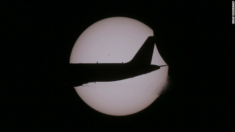 An Air Asia passenger plane flies past the sun as a partial eclipse occurs, seen from Taguig city, east of Manila, Philippines.