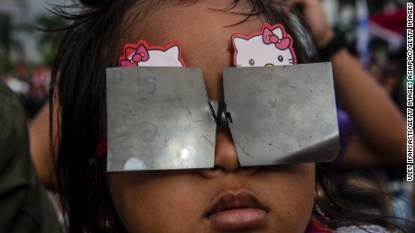 PALEMBANG, SUMATRA, INDONESIA - MARCH 09:  A girl watches the total solar eclipse in Palembang city on March 9, 2016 in Palembang, South Sumatra province, Indonesia. A total solar eclipse swept across Indonesia on Wednesday, seen by sky gazers and marked by parties, colourful tribal rituals and Muslim prayers.  (Photo by Ulet Ifansasti/Getty Images)