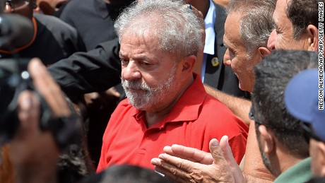 """Former Brazilian President Luiz Inacio Lula da Silva meets supporters gathering outside his house to show him their support, in Sao Bernardo do Campo, near Sao Paulo, Brazil, on March 5, 2016. Brazil's ex-president Lula da Silva vowed to battle his opponents in the streets in a defiant speech late Friday, hours after being briefly detained as part of a probe into a massive corruption scheme. Prosecutors said Lula was targeted as part of the Operation Car Wash investigation into a sprawling embezzlement and bribery conspiracy centred on the state oil giant Petrobras. Lula was not arrested, but held for questioning over alleged """"favors"""" received from corrupt construction companies implicated in a kickback scheme, prosecutors said.   AFP PHOTO / NELSON ALMEIDA / AFP / NELSON ALMEIDA        (Photo credit should read NELSON ALMEIDA/AFP/Getty Images)"""