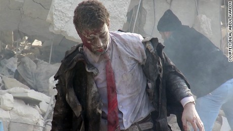 A man emerges from the wreckage of a courthouse in rebel-held Idlib, Syria after it was hit by airstrikes in December 2015.