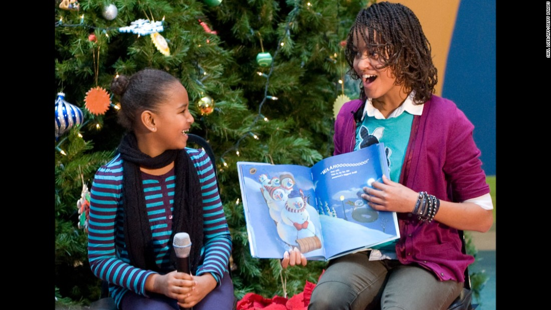 "Malia, right, and Sasha read the book ""Snowmen at Night"" by Caralyn Buehner to children during a visit to the Children's National Medical Center in Washington on December 22, 2009."
