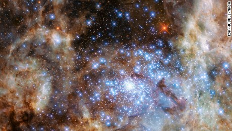 The image shows the central region of the Tarantula Nebula in the Large Magellanic Cloud. The young and dense star cluster R136 can be seen at the lower right of the image. This cluster contains hundreds of young blue stars, among them the most massive star detected in the Universe so far. Using the NASA/ESA Hubble Space Telescope astronomers were able to study the central and most dense region of this cluster in detail. Here they found nine stars with more than 100 solar masses.