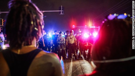 St. Louis County Police and Missouri State Highway Patrol troopers (C) stand guard as protesters (foreground) march on West Florissant Avenue in Ferguson, Missouri on August 9, 2015.  A day of peaceful remembrance marking the anniversary of 18-year-old black teen Michael Brown's killing by police in the US city of Ferguson came to a violent end on August 9 as gunfire left at least one protester injured.       AFP PHOTO / MICHAEL B. THOMAS        (Photo credit should read Michael B. Thomas/AFP/Getty Images)