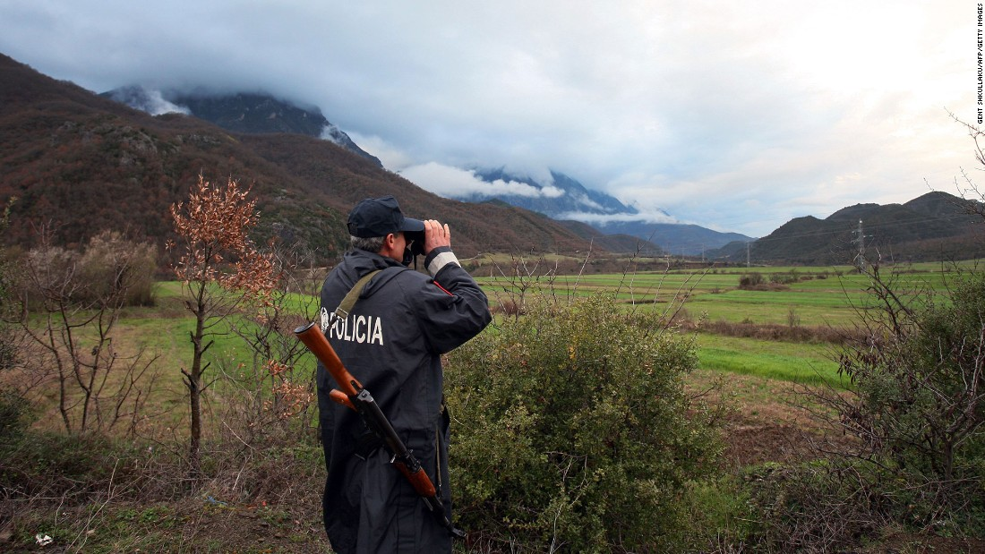 An Albanian police officer patrols near the Greek border in Carshove on Tuesday, March 15.