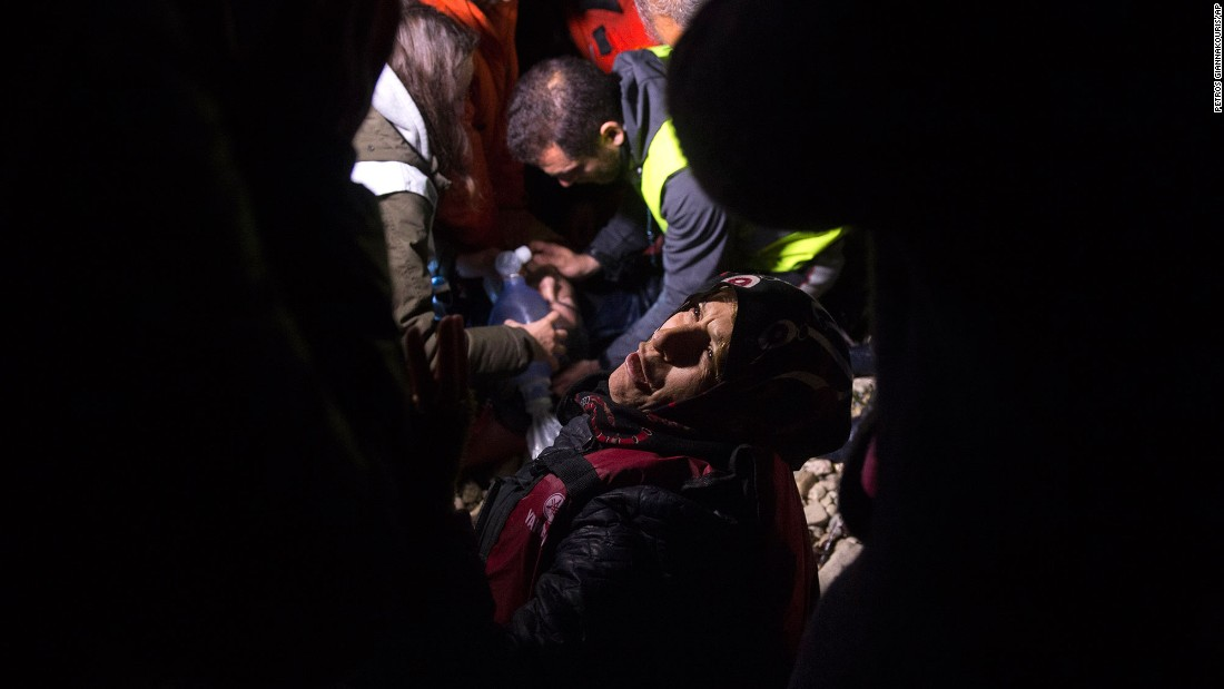 A woman reacts as volunteers try to revive her husband after an overcrowded boat, carrying dozens of migrants and refugees from nearby Turkey, arrived on the Greek island of Lesbos on Sunday, March 20.