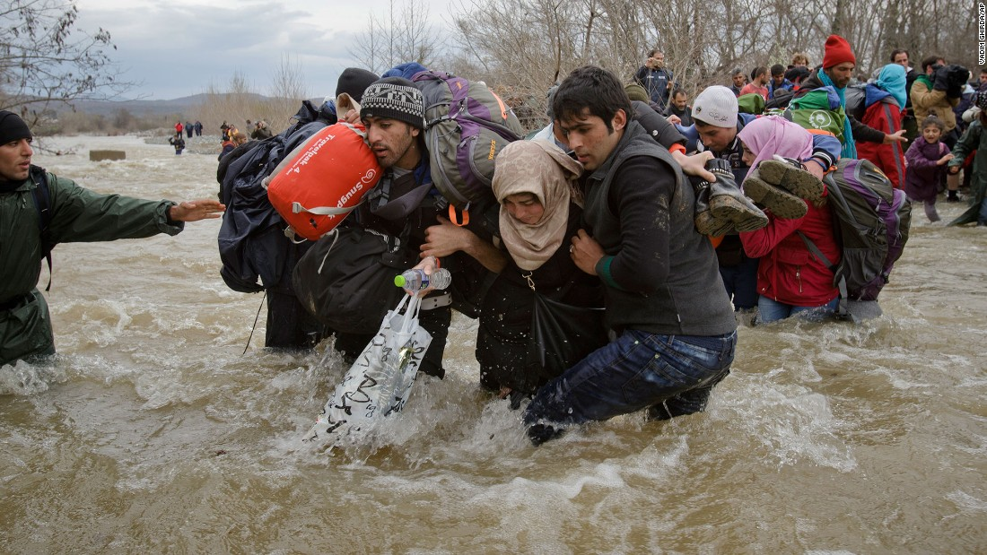 Migrants stumble as they cross a river north of Idomeni, Greece, attempting to reach Macedonia on a route that would bypass the border control fence on Monday, March 14.