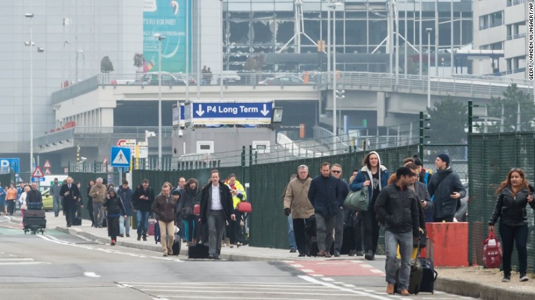 People walk away from Brussels airport after explosions rocked the facility.
