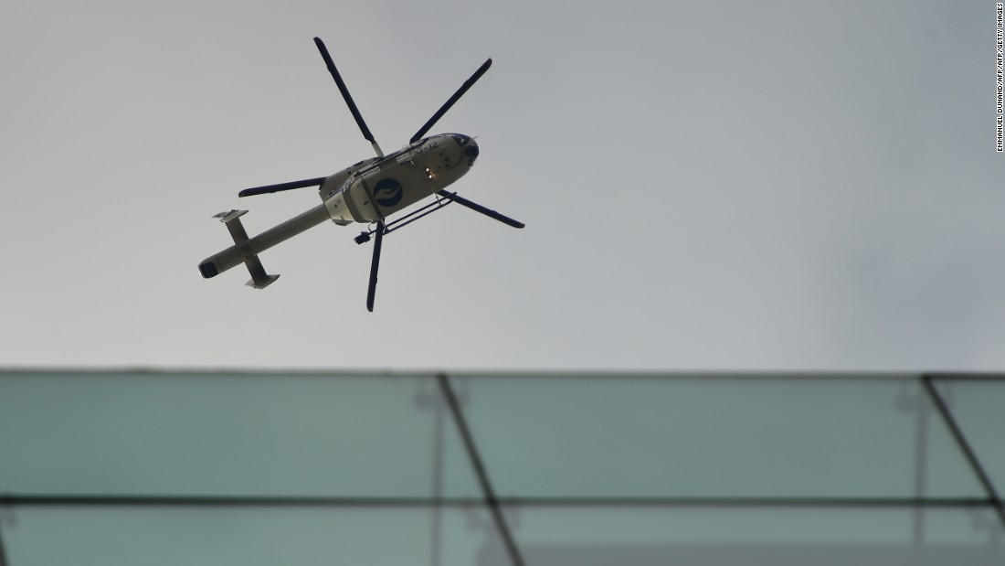 A police helicopter flies above the area near the subway station.