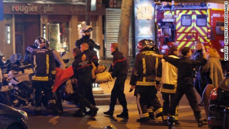 Medics move a wounded man near the Boulevard des Filles-du-Calvaire after an attack November 13, 2013 in Paris, France.