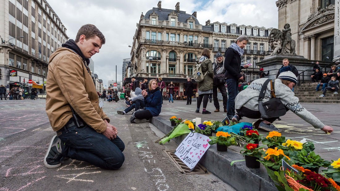 A man looks at flowers and messages outside the stock exchange in Brussels on March 22.