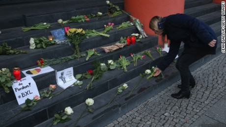 A woman lays flowers at the steps of the Belgian Embassy in Berlin.