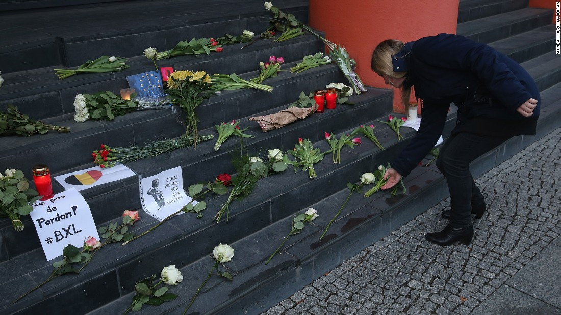 A woman lays flowers at the steps of the Belgian Embassy in Berlin on March 22.