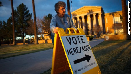 Election day volunteer Vicki Groff places a sign to direct voters to a polling station at Kenilworth School February 28, 2012 in Phoenix, Arizona.