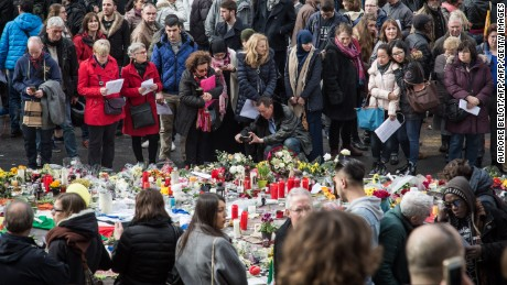 People gather at the makeshift memorial on Place de la Bourse square in Brussels to pay tribute to the victims of the Brussels terror attacks, on March 25, 2016.  Grieving Belgians were holding prayers in the rain in a central Brussels square carpeted with flowers and tributes to the 31 killed and 300 injured by the airport and metro suicide blasts on March 22. The Belgian government faces heavy criticism over how the Brussels attackers slipped through the net, with three of them known to police and said to have links to the November Paris attacks in which 130 people died. / AFP / BELGA / Aurore Belot / Belgium OUT        (Photo credit should read AURORE BELOT/AFP/Getty Images)