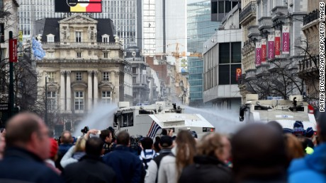 Police use water cannons to disperse anti-immigration protesters at a memorial site for victims of Brussels attacks.