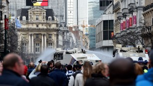 Police use water cannons to disperse anti-immigration protesters at a memorial site for victims of the Brussels attacks.