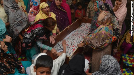 """Pakistani relatives mourn over the body of a victim during a funeral following an overnight suicide bombing in Lahore on March 28, 2016.  The toll from a suicide blast in Pakistan's Lahore rose to 69, officials said on March 28, as authorities hunted for the """"savage inhumans"""" behind the attack in a park packed with Christian families celebrating Easter Sunday. More than 200 people were injured, many of them children, when explosives packed with ball bearings ripped through crowds near a children's play area in the park in Lahore, leaving dozens dead or bloodied. / AFP / ARIF ALI        (Photo credit should read ARIF ALI/AFP/Getty Images)"""