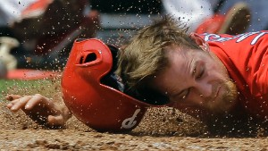 Philadelphia Phillies' Ryan Jackson loses his helmet as he hits the dirt after getting tagged out by Detroit Tigers catcher Jarrod Saltalamacchia during the third inning of a spring training baseball game Saturday, March 26, 2016, in Clearwater, Fla. Jackson was out trying to score on a fly out by Andres Blanco to Tigers right fielder Tyler Collins. (AP Photo/Chris O'Meara)