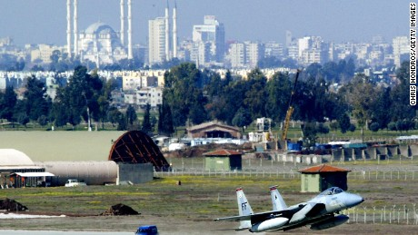 An F-15 fighter jet glides in for a landing in front of Adana's main mosque March 7, 2003 at Incirlik Air Force Base in Turkey.