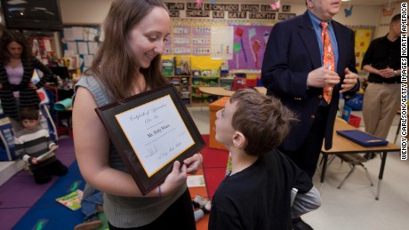 """WESTON, CT - APRIL 26:   Pre-kindergartner teacher Holly Mora shows an appreciation plaque to student,  Alexander Parnas, that was presented to her by children's author, Alan Katz, right, during OfficeMax's """"A Day Made Better"""" presentation at Hurlbutt Elementary School on April 26, 2010 in Weston, Connecticut.   (Photo by Wendy Carlson/Getty Images for OfficeMax)"""