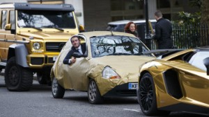 A The Sun reporter parks his Ford KA covered with golden wrapping paper next to fleet of supercars covered in gold chrome wrap parked in Knightsbridge, London Golden supercars in Kensington, London, Britain - 30 Mar 2016 Cars believed to be owned by a tourist from Saudi Arabia  (Rex Features via AP Images)