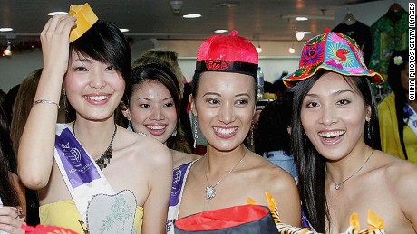 Contestants of 2005 Miss Tourism Queen International, Olivia Laniova from Slovak Republic (L), Sun Jia from China (2nd from L), Sheila Alonso from Philippines (2nd from R) and Ngo Thi Thanh Ngan from Vietnam (R) pose for pictures with traditional hats as they take in the sites of Beijing on June 8, 2005 in Beijing, China. Seventy-five contestants from around the world have gathered in Beijing for a four-day sightseeing and welfare activities. The finals of the pageant will be held in Hangzhou of Zhejiang Province on July 2, 2005.(Photo by China Photos/Getty Images)