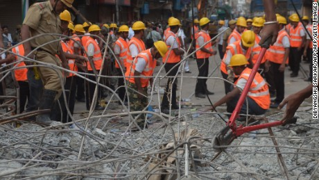 Indian rescue workers try to free people trapped under the wreckage of a collapsed flyover bridge in Kolkata on April 1, 2016.   Emergency workers in India battled to rescue dozens of people still trapped after a flyover collapsed onto a busy street, killing at least 22 people and injuring over 100 more. / AFP / Dibyangshu SARKAR        (Photo credit should read DIBYANGSHU SARKAR/AFP/Getty Images)