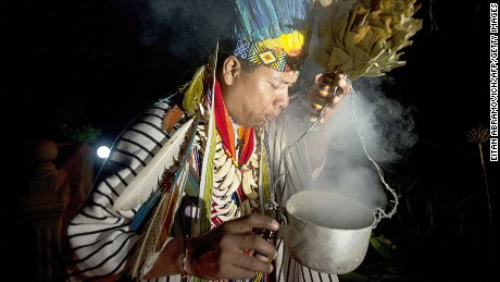 Picture taken on August 09, 2014, of a healer starting a Yage ceremony by offering what they call the medicinal plant to a person taking part of the ritual, in La Calera, Cundinamarca department, Colombia. Yage, a mixture of the Ayahuasca hallucinogenic liana and a psychoactive bush, attracts many people in Colombia, who seek to participate in a traditional indigenous ritual of spiritual and physical healing impossible to realize in many countries where these plants are considered drugs. AFP PHOTO/EITAN ABRAMOVICH (Photo credit should read EITAN ABRAMOVICH/AFP/Getty Images)