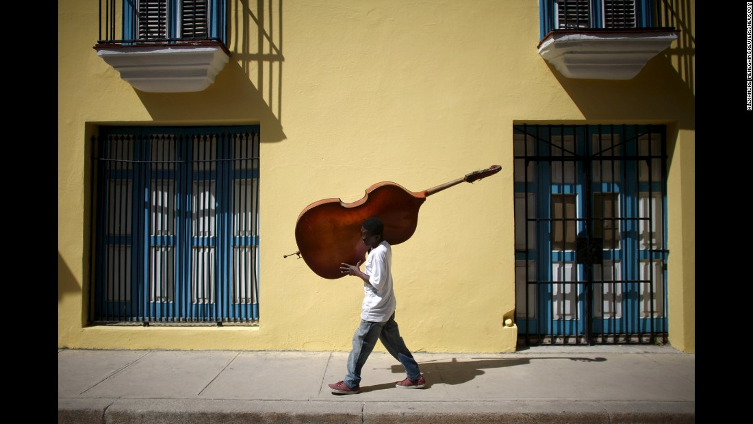 Musician Frilal Ortiz carries a double bass through downtown Havana. In March, Barack Obama became the first U.S. president to visit Cuba since Calvin Coolidge stopped by in 1928.