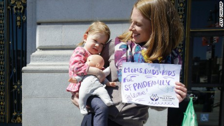 Kim Turner holds her daughter Adelaide Turner Winn before a rally supporting paid family leave at City Hall in San Francisco on April 5.