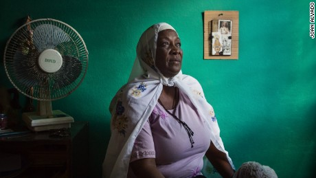 Elsa Morales, a Cuban woman now known with the Muslim name of Fatima, seen in her bedroom, with a Jesus Crist image in the background. Elsa is the only Muslim member of her family.