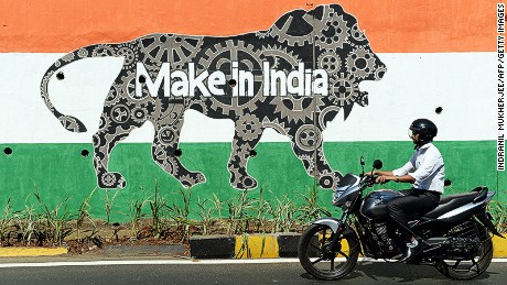 An Indian motorist rides past a wall bearing the image of the mascot for 'Make in India Week' in Mumbai on February 12, 2016. Over 190 companies, and 5,000 delegates from 60 countries, are due to take part in the first 'Make in India' week to be held in Mumbai from February 13-18. AFP PHOTO / INDRANIL MUKHERJEE / AFP / INDRANIL MUKHERJEE (Photo credit should read INDRANIL MUKHERJEE/AFP/Getty Images)