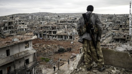 A Kurdish marksman stands atop a building as he looks at the destroyed Syrian town of Kobani on January 30, 2015. Kurdish forces recaptured the town on the Turkish frontier on January 26, in a symbolic blow to the jihadists who have seized large swathes of territory in their onslaught across Syria and Iraq.