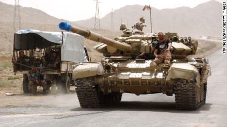Syrian pro-governement forces drive a tank on the outskirts of Palmyra on March 25, 2016, during a military operation to retake the ancient city from the jihadist Islamic State (IS) group.
