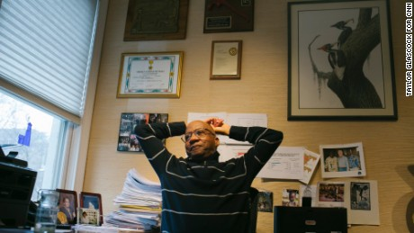 Dr. Donald Hopkins stretches in his home, surrounded by  his many honors and degrees and images of woodpeckers , a favorite animal of his Wednesday Feb. 24, 2016 in Chicago, Ill. (Taylor Glascock/for CNN)